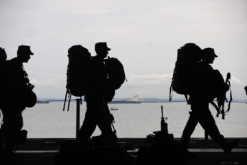 military persons and veterans walking with gear